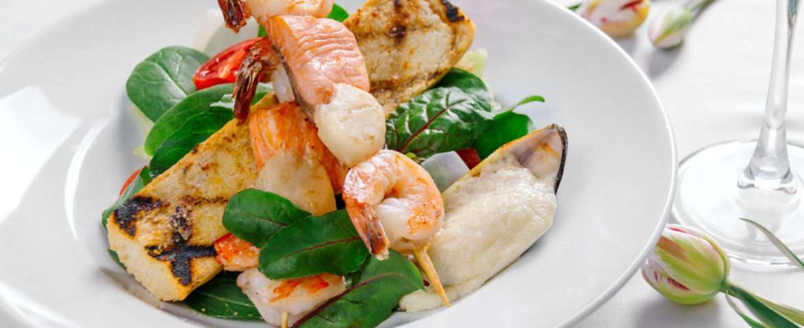 Grilled salad with tiger shrimps, scallops, salmon